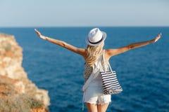La ragazza esamina il mare, stante su una roccia Immagini Stock