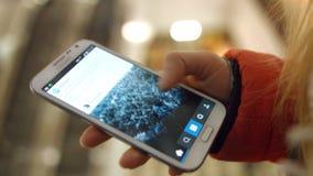 La ragazza esamina il primo piano delle foto delle applicazioni e di sguardo del telefono cellulare 4K 30fps ProRes archivi video