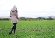 La ragazza esamina l'autunno nel prato del Th fotografia stock