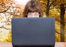 La ragazza esamina la copertura del computer portatile in legno di autunno Immagine Stock