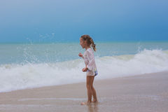 La ragazza esamina la distanza l'oceano sulla spiaggia in un infuriarsi della tempesta Fotografia Stock Libera da Diritti