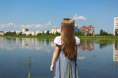 La ragazza esamina la distanza nel lago fotografia stock