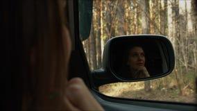 La ragazza esamina la foresta nell'automobile video d archivio