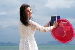 La ragazza esamina la macchina fotografica sulla spiaggia con ipad fotografia stock