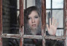 La ragazza esamina la vecchia finestra Fotografia Stock