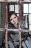 La ragazza esamina la vecchia finestra Fotografie Stock