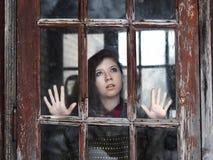 La ragazza esamina la vecchia finestra Immagine Stock Libera da Diritti