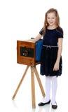 La ragazza esamina la vecchia macchina fotografica immagine stock