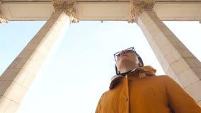 La ragazza esamina le alte colonne Cielo blu Movimento lento video d archivio