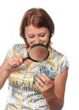 La ragazza esamina un regalo tramite un magnifier Fotografie Stock