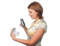 La ragazza esamina un regalo tramite un magnifier Fotografia Stock