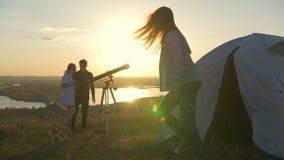 La ragazza esce dalla tenda agli amici ad osservare tramite il telescopio il tramonto dell'estate video d archivio