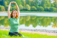 La ragazza esegue l'allungamento dei muscoli dorsali di esercizi Fotografia Stock