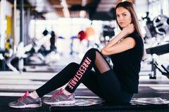 La ragazza esile attraente che fa l'allungamento si esercita sulla stuoia nera nella palestra moderna di forma fisica La ragazza  fotografia stock