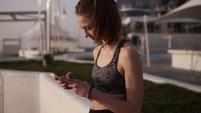 La ragazza esile e attraente negli sport copre l'esame del telefono cellulare che si appoggia un parapetto bianco seaside Rilassa archivi video