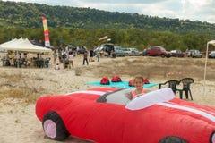 La ragazza esplora un aquilone rosso a forma di auto enorme Immagini Stock Libere da Diritti