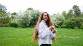 La ragazza europea con capelli ricci molto lunghi lascia le bolle e funziona sulla natura Il giovane modello femminile sta divert archivi video