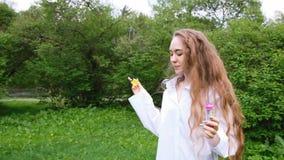 La ragazza europea con capelli ricci molto lunghi lascia le bolle e funziona sulla natura Modello femminile sexy divertendosi nel video d archivio