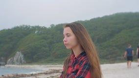 La ragazza europea rilassata vestita in camicia a quadretti sta sedendosi sulla spiaggia il giorno nuvoloso archivi video