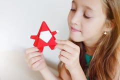 La ragazza fa gli origami di Natale Santa Claus, abete immagini stock libere da diritti
