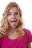La ragazza fa il fronte divertente in primo piano sopra fondo bianco Immagine Stock Libera da Diritti
