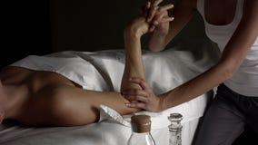 La ragazza fa il massaggio di rilassamento della mano con olio video d archivio
