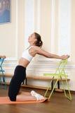 La ragazza fa l'allungamento dell'esercizio di yoga Immagine Stock