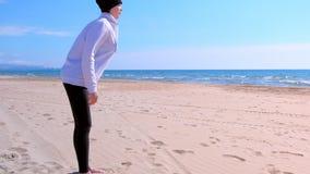 La ragazza fa le inclinazioni sugli esercizi di sport all'aperto di forma fisica della spiaggia della sabbia di mare su addestram stock footage