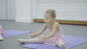 La ragazza fa la metà del corpo spaccato piegato durante la classe di balletto in bello studio video d archivio