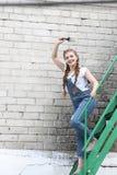 La ragazza fa la preparazione per la verniciatura del gazebo di superficie di legno, recinto fotografia stock