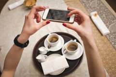 La ragazza fa un'immagine di due tazze con caffè, primo piano Fotografia Stock