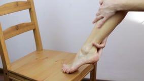 La ragazza fa un massaggio del piede dopo la procedura della depilazione archivi video