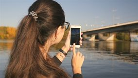 La ragazza fa una foto sul telefono Bella natura Fiume con un ponte Giorno pieno di sole Movimento lento video d archivio