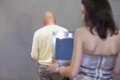 La ragazza fa una fotografia dell'uomo Fotografia Stock Libera da Diritti