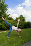La ragazza fa una rotella su un'erba. Fotografie Stock Libere da Diritti