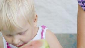 La ragazza favorita fresca per 2-3 anni mangia l'anguria Bambino rurale, video casalingo sveglio stock footage
