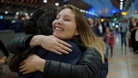 La ragazza felice abbraccia il suo amico all'arrivo su una stazione ferroviaria - colpo del movimento lento video d archivio