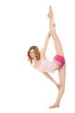 La ragazza felice in abiti sportivi fa l'esercitazione relativa alla ginnastica Fotografie Stock Libere da Diritti