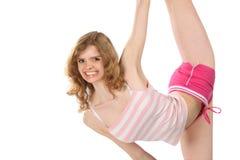La ragazza felice in abiti sportivi fa l'esercitazione relativa alla ginnastica Fotografia Stock Libera da Diritti