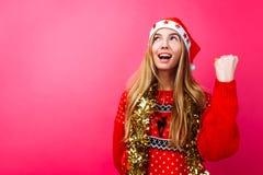 La ragazza felice in cappello di Santa e con lamé sul suo collo, descrive un gesto di successo e della vittoria, su un fondo ross immagine stock