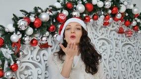 La ragazza felice in cappello rosso di Santa invia l'aria che bacia esaminando la macchina fotografica in studio decorato Natale archivi video