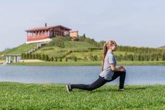 La ragazza felice che fa l'allungamento si esercita nel parco dell'estate Fotografia Stock Libera da Diritti