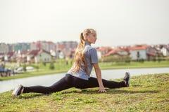 La ragazza felice che fa l'allungamento si esercita nel parco dell'estate Fotografia Stock