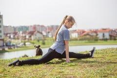 La ragazza felice che fa l'allungamento si esercita nel parco dell'estate Immagini Stock Libere da Diritti