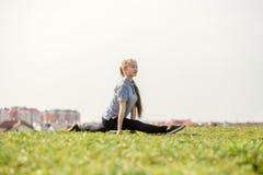 La ragazza felice che fa l'allungamento si esercita nel parco dell'estate Immagini Stock