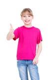 La ragazza felice che mostra i pollici aumenta il gesto. Fotografia Stock