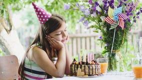 La ragazza felice che si siede alla tavola nel giardino ed ammira un dolce festivo stock footage