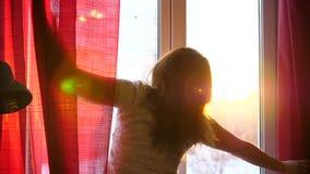 La ragazza felice che viene alla finestra, apre le tende I raggi del ` s del sole attraversano la finestra, illuminante la stanza stock footage