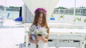La ragazza felice con i fiori in mani addolcisce sorridere alla barra di baia lentamente video d archivio
