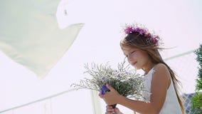 La ragazza felice con i fiori in mani addolcisce sorridere alla barra di baia lentamente archivi video